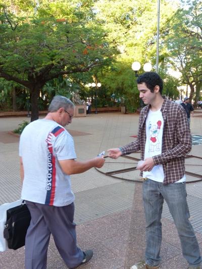 Sebastián reparte folletos con su historia de vida en la plaza 9 de Julio.