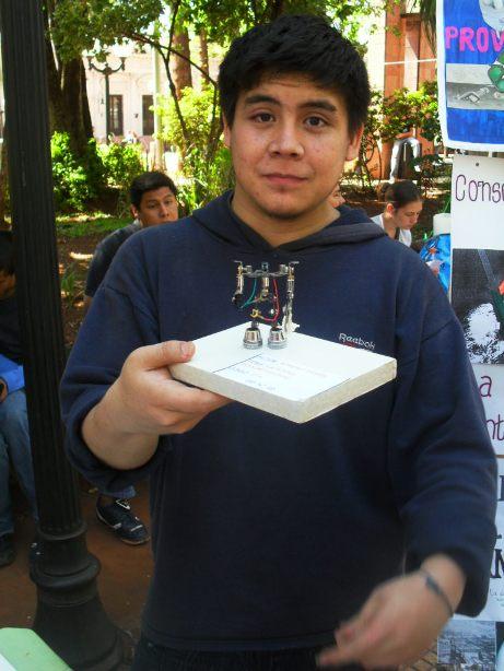 El alumno Daniel Romero expone sus robots en la plaza 9 de Julio.