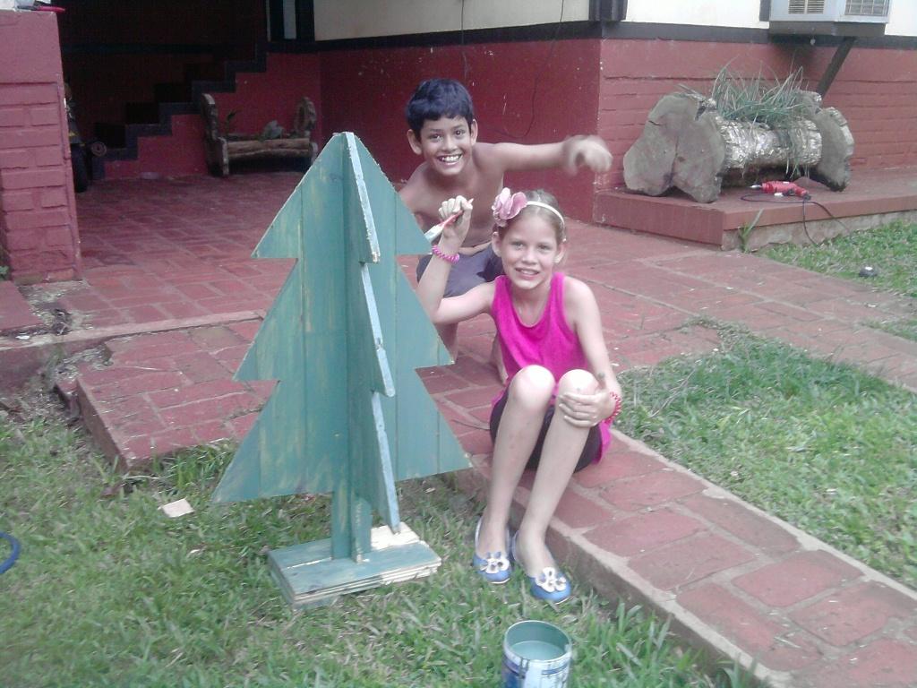 Yamila y Hernán pintan un arbolito no convencional de Navidad.