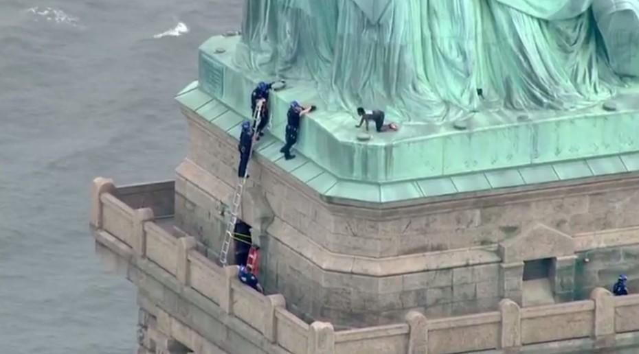 Una mujer escala la Estatua de la Libertad para protestar contra las políticas migratorias de Donald Trump
